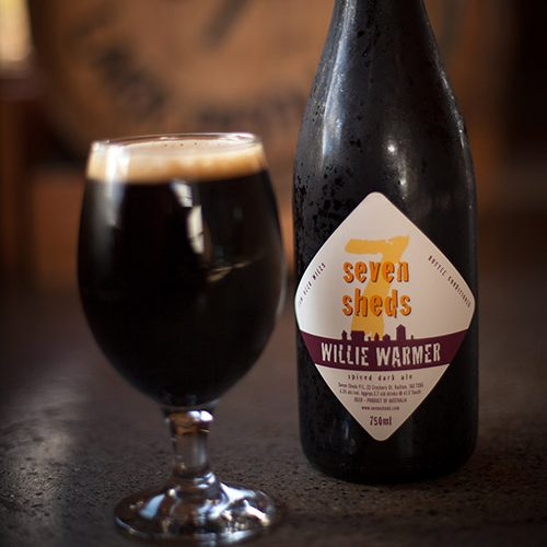 A glass of Willie Warmer dark ale beside its packaged 750ml bottle