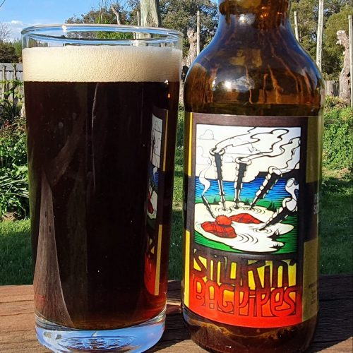 Image shows a glass of Smokin Bagpipes sitting beside the bottle it has just been poured from, background is the hop garden in Spring.
