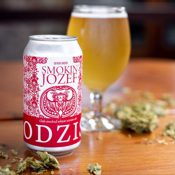 This image shows a Seven Sheds Grodziskie can beside a glass of the same beer with crushed hops scattered around them.