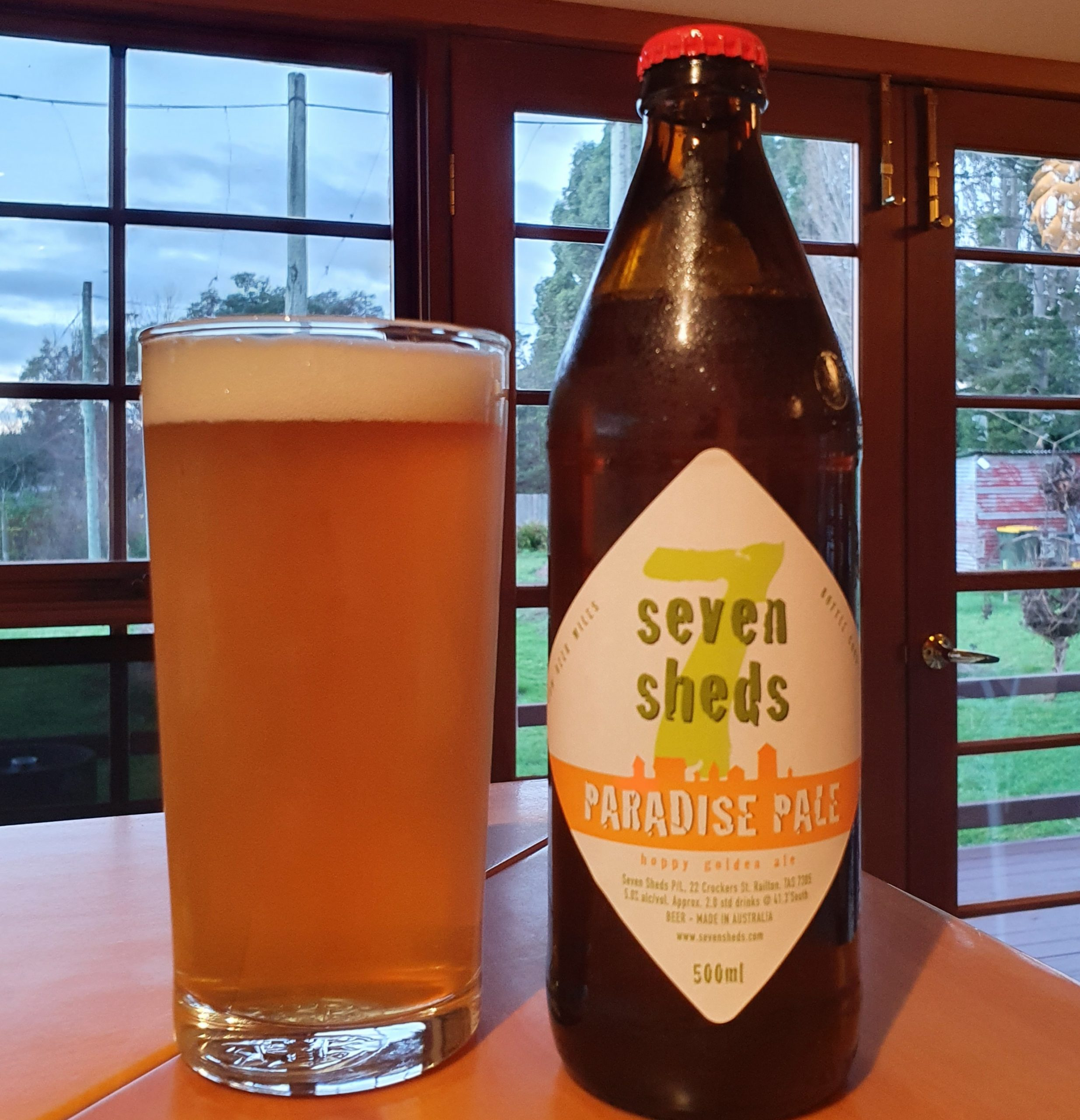500ml bottle of Seven Sheds Paradise Pale beside a glass of Paradise Pale